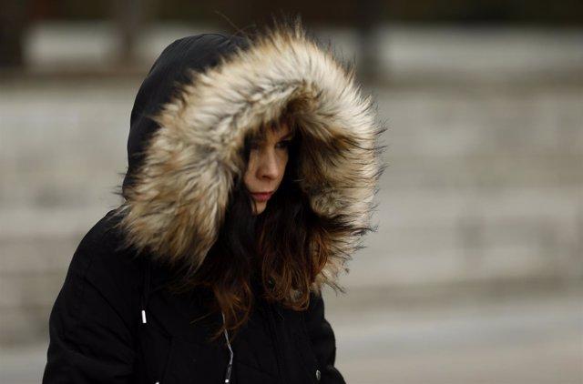 Una joven camina por la calle un día de invierno