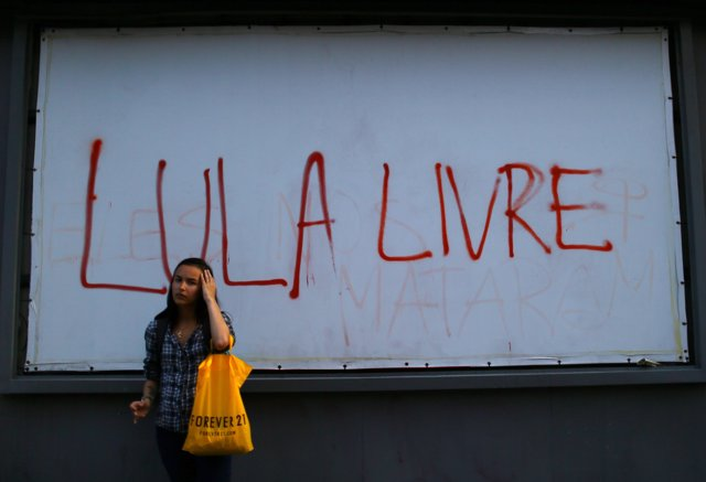 "A woman stands in front of a sign reading: ""Lula free"" referring to  former Braz"