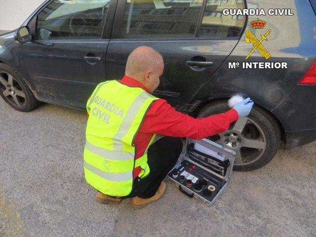Un agente de Guardia Civil examina un vehículo dañado