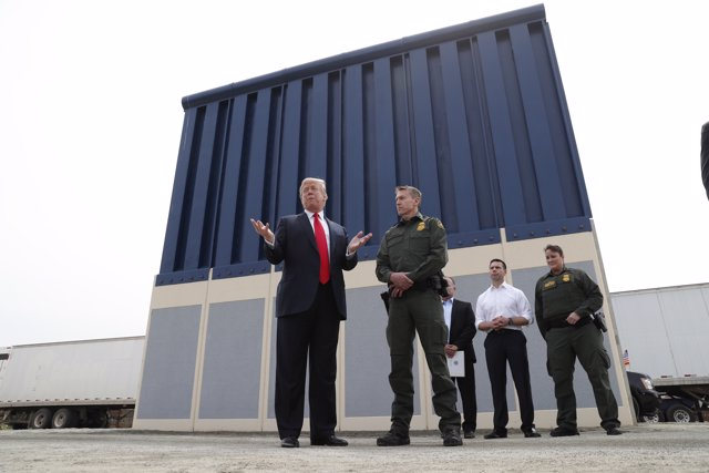 U.S. President Donald Trump talks with a U.S. Customs and Border Protection (CBP