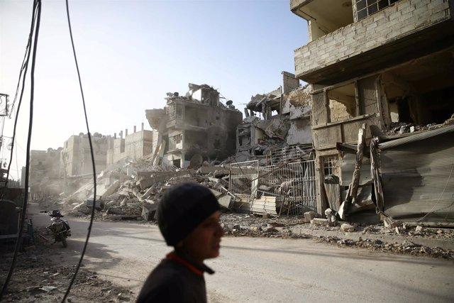 Un niño cerca de edificios dañados en la ciudad sitiada de Duma, en Ghuta