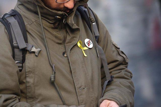 Una persona con lazo amarillo y chapa de libertad para los presos políticos