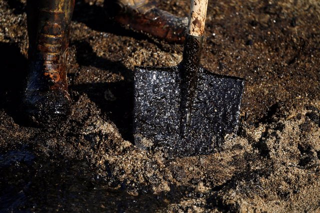 A worker's shovel is covered with oil that leaked from a small oil tanker that s
