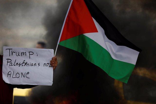 Un manifestante exhibe una bandera palestina frente a militares israelíes