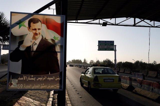 Cartel con la imagen de Bashar al Assad en Damasco
