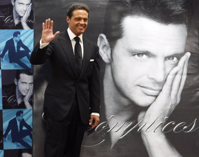 Mexican singer Luis Miguel poses next to a poster of himself during a photocall
