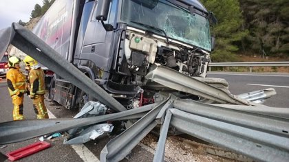 Un camión cargado de motos choca y queda atravesado por el quitamiedos en la AP-7