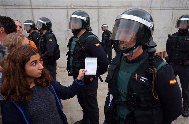 Un agente de la Guardia civil, frente a una votante durante el 1-O