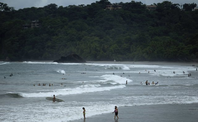 Tourists spend their day in the sea on the beach at Manuel Antonio National Park
