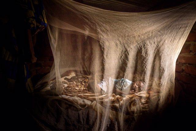 Un niño duerme bajo una mosquitera en Burundi