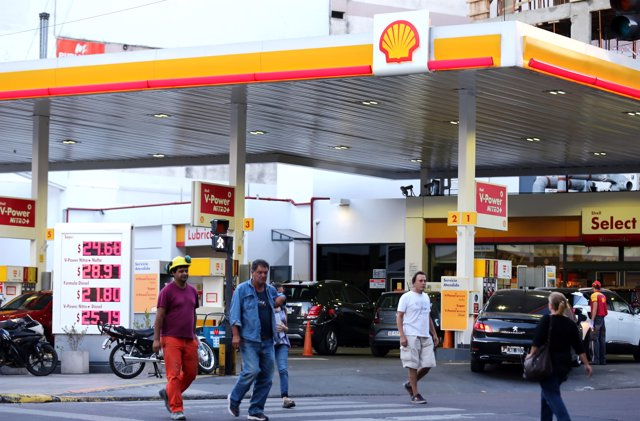 People walk in front of a Shell gas station in Buenos Aires, Argentina, March 12