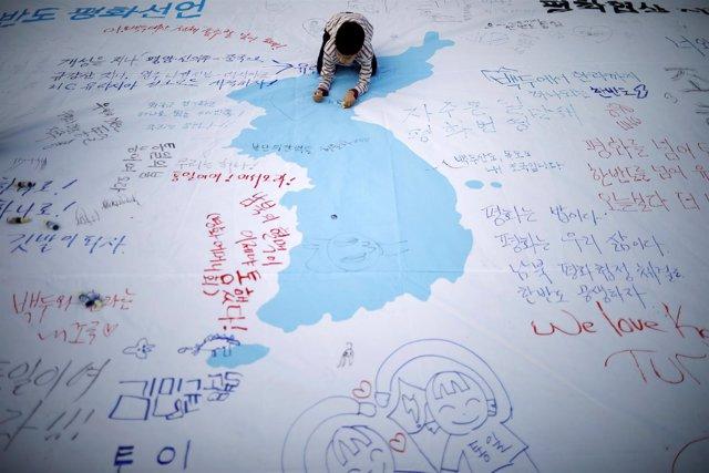 Un niño escribe un mensaje en una bandera de unificación coreana