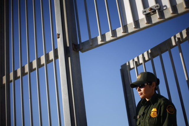 A United States Border Patrol agent keeps watch from a secondary wall separating