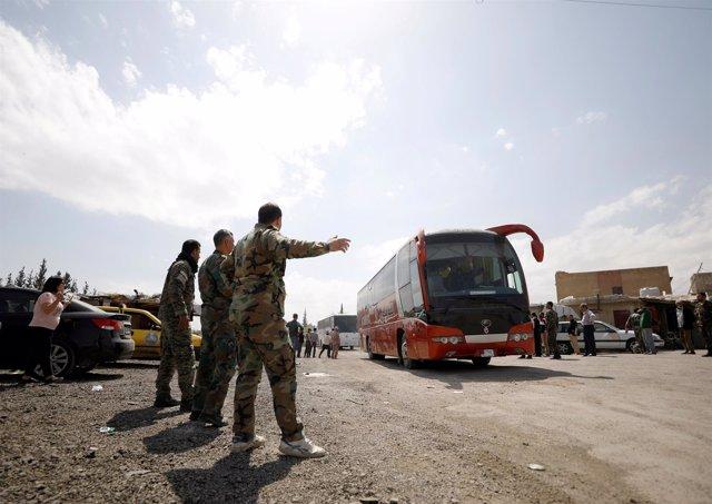 Rebeldes sirios y sus familias salen en un autobús del campo de Wafideen