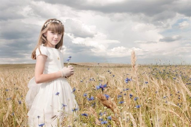 Foto de archivo de una niña en un vestido de comunión