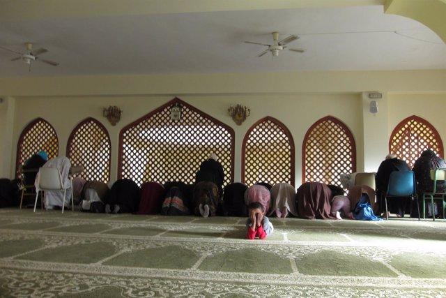 Niño junto a mujeres rezando en una mezquita