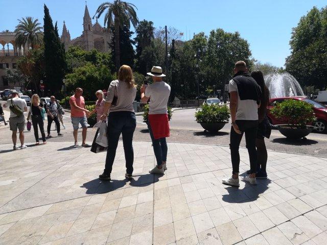 Turistas tomándose fotos en el Paseo del Borne con la catedral al fondo