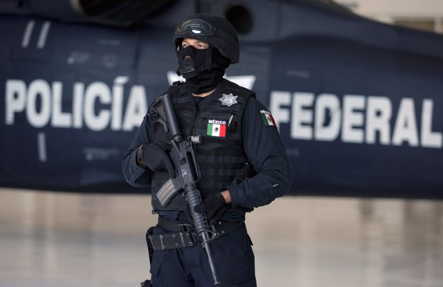 A Mexican federal policeman stand guards during a presentation of four suspected
