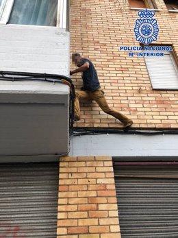 Imagen de uno de los jóvenes, encaramado a una fachada durante su huida