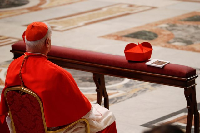 A Cardinal sits inside the St. Peter's Basilica before celebrating the Sacrament