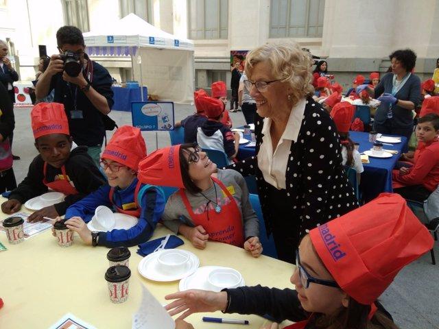 Manuela Carmena con un grupo de escolares desayunando