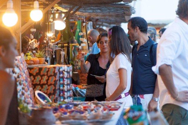 Turistas en un mercado artesano en Formentera