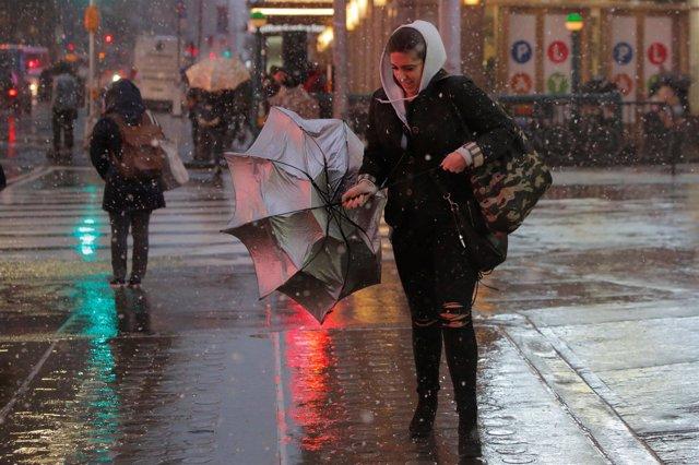 Una mujer lucha contra el viento con un paraguas