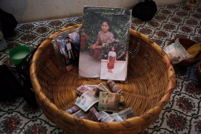 A basket is seen with banknotes and pictures of Claudia Gomez, a 19-year old Gua