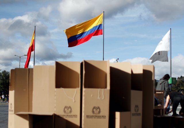The Colombian flag is seen as people assemble voting booths ahead of the May 27