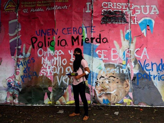 Manifestante ante un mural contra el Gobierno y la Policía de Nicaragua