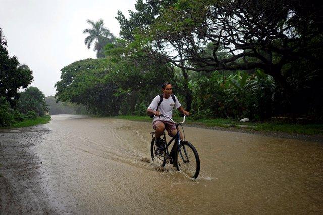 Un hombre monta en bicicleta por un camino inundado por 'Alberto' en Cuba