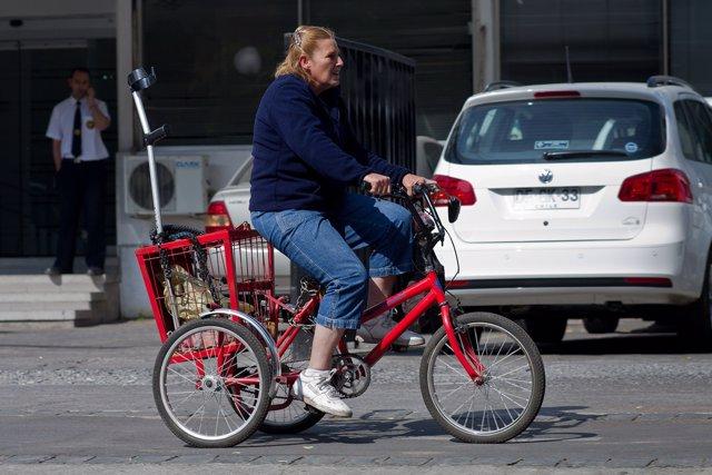 Mujer en bicicleta y con una muleta