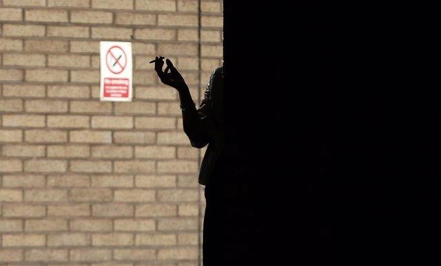 """Una mujer fuma frente a una señal de """"No fumar"""""""