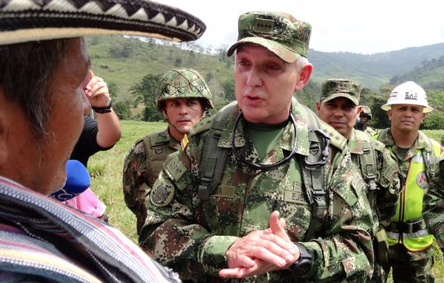 Alberto Mejia, Commander of the Colombian National Army, talks to a peasant duri
