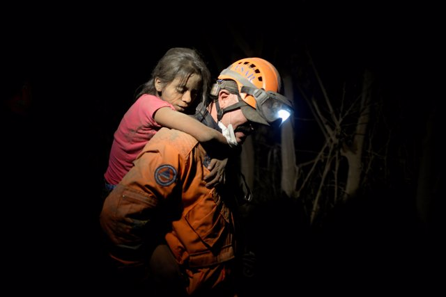A rescue worker carries a child covered with ash after Fuego volcano erupted vio