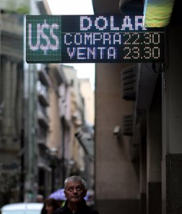A man looks at an electronic board showing currency exchange rates in Buenos Air