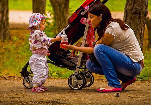 Madre e hija, bebé, cochecito de bebé, biberón