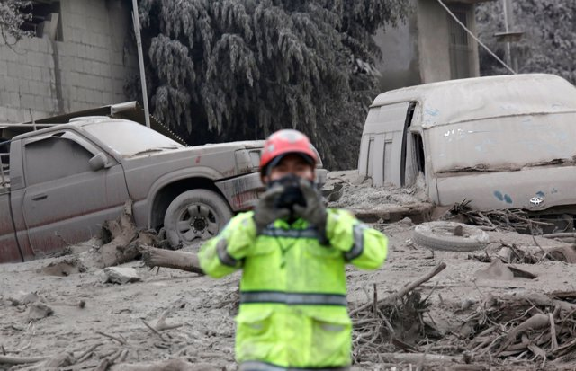 Vehicles damaged by an eruption from Fuego volcano are seen beside a firefighter