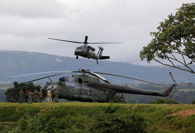 Soldiers of the Colombian Military Forces make a flyby during the army's arrival