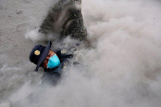 Un policía se tropieza mientras corre por la erupción del Volcán de Fuego