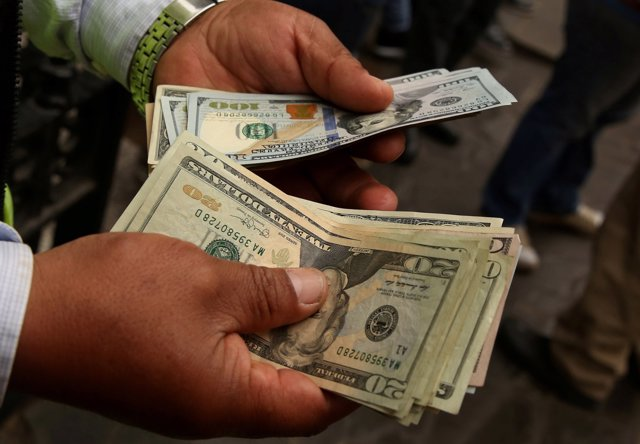 FILE PHOTO:    A money changer holds U.S. Dollar bills at a street in downtown L