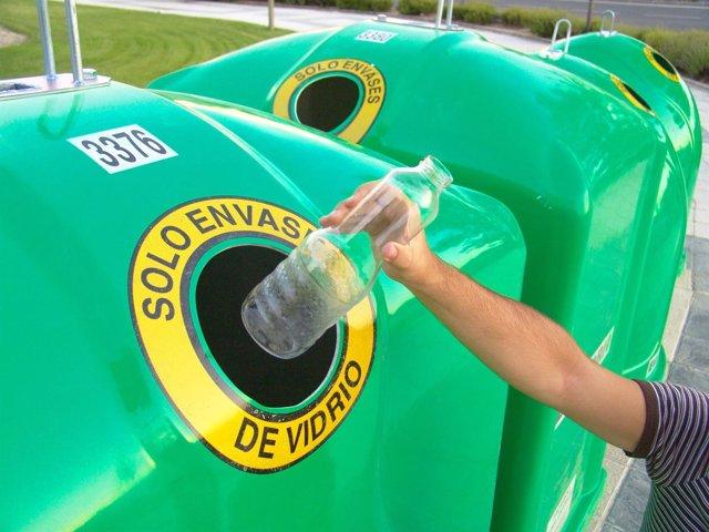 Ciudadano reciclando vidrio en el contenedor verde