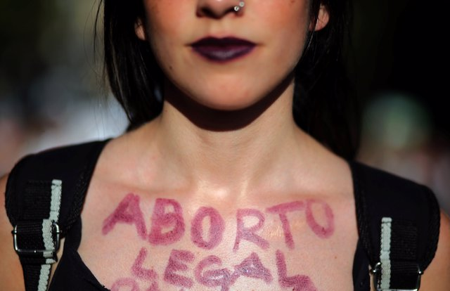 "A woman shows the words ""Legal abortion"" written on her chest during a demonstra"
