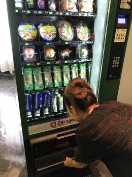 Una joven adquiere un producto saludable de una máquina expendedora