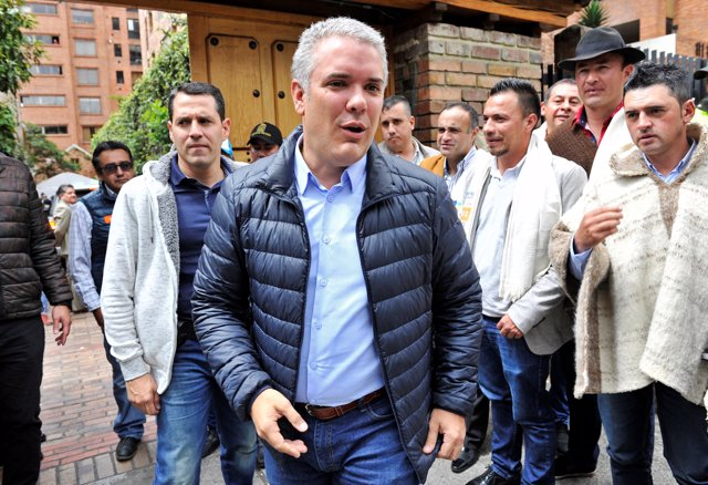 Colombian presidential candidate Ivan Duque (C) greets followers at his party's