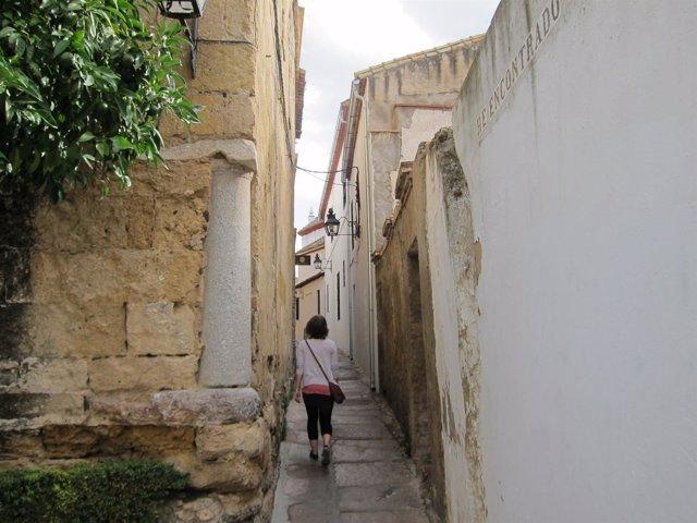 Una mujer pasea por una calleja del casco histórico de Córdoba