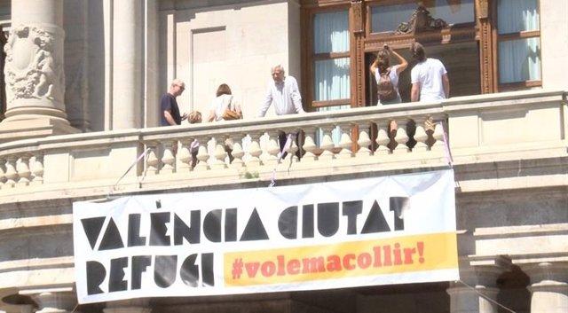 Joan Ribó en el balcón del Ayuntamiento junto a la pancarta de ciudad refugio