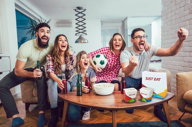 Gente animando partido de fútbol con comida a domicilio
