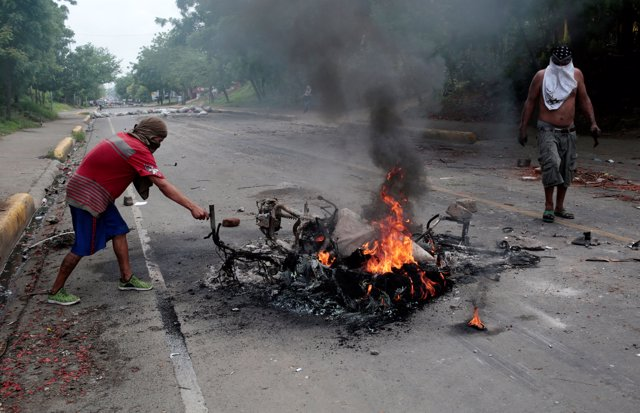 Protester stand next to a burned motorcycle during a protest against Nicaragua's