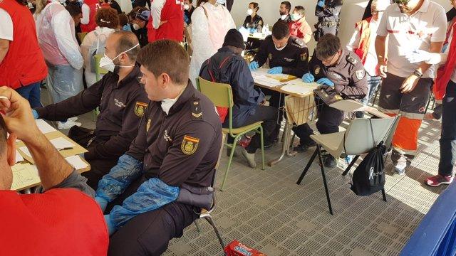 Policías documentando a los migrantes del Dattilo, el primer barco en llegar